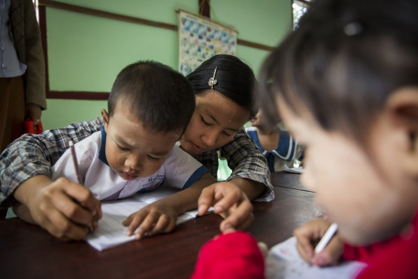 A teacher helps a child colour in during an activity at St Teresa's Pre School at Oatshipin town outside Pyey. The RNDM Sisters run a number of pre schools in and around the city of Pyey in Myanmar.